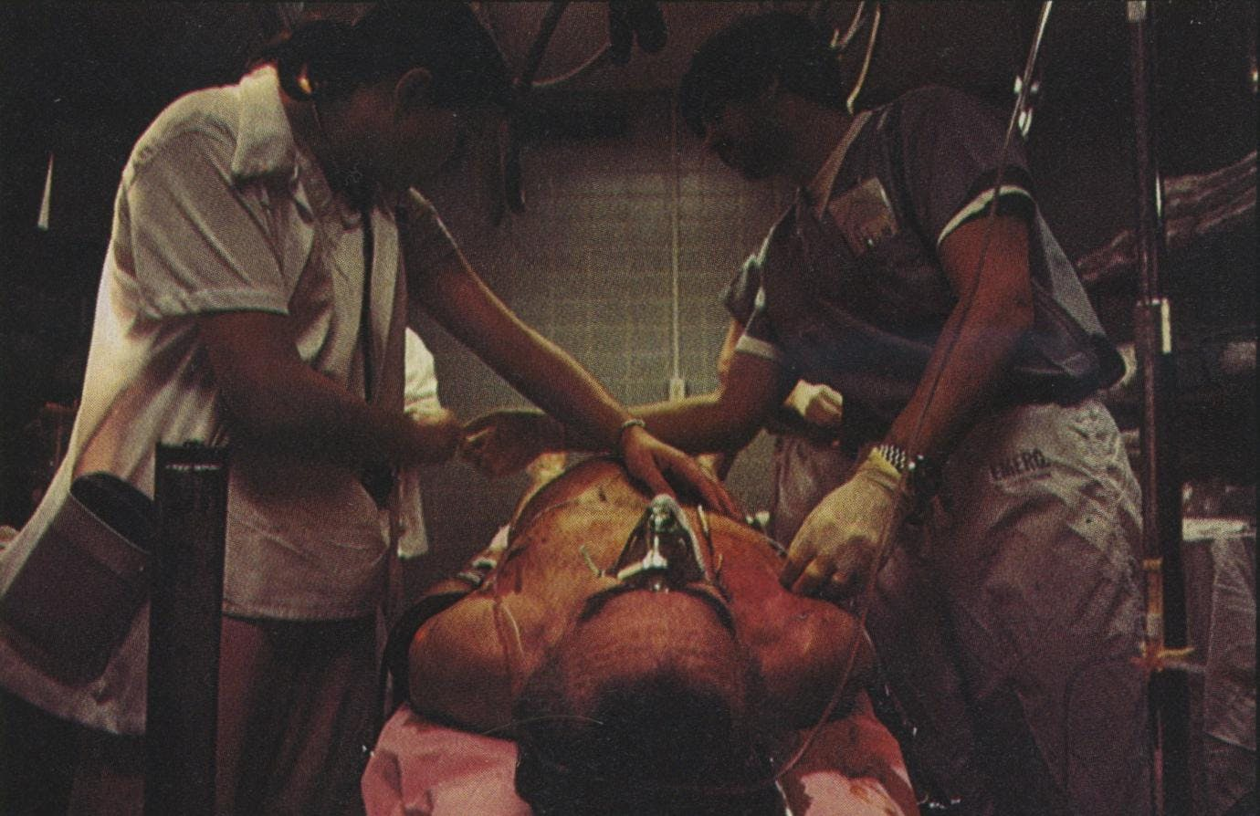 Residents start IVs in this victim's chest in order to mainline lifesaving fluids to his shocked system. The swelling of the lower abdomen is caused by extensive internal bleeding.