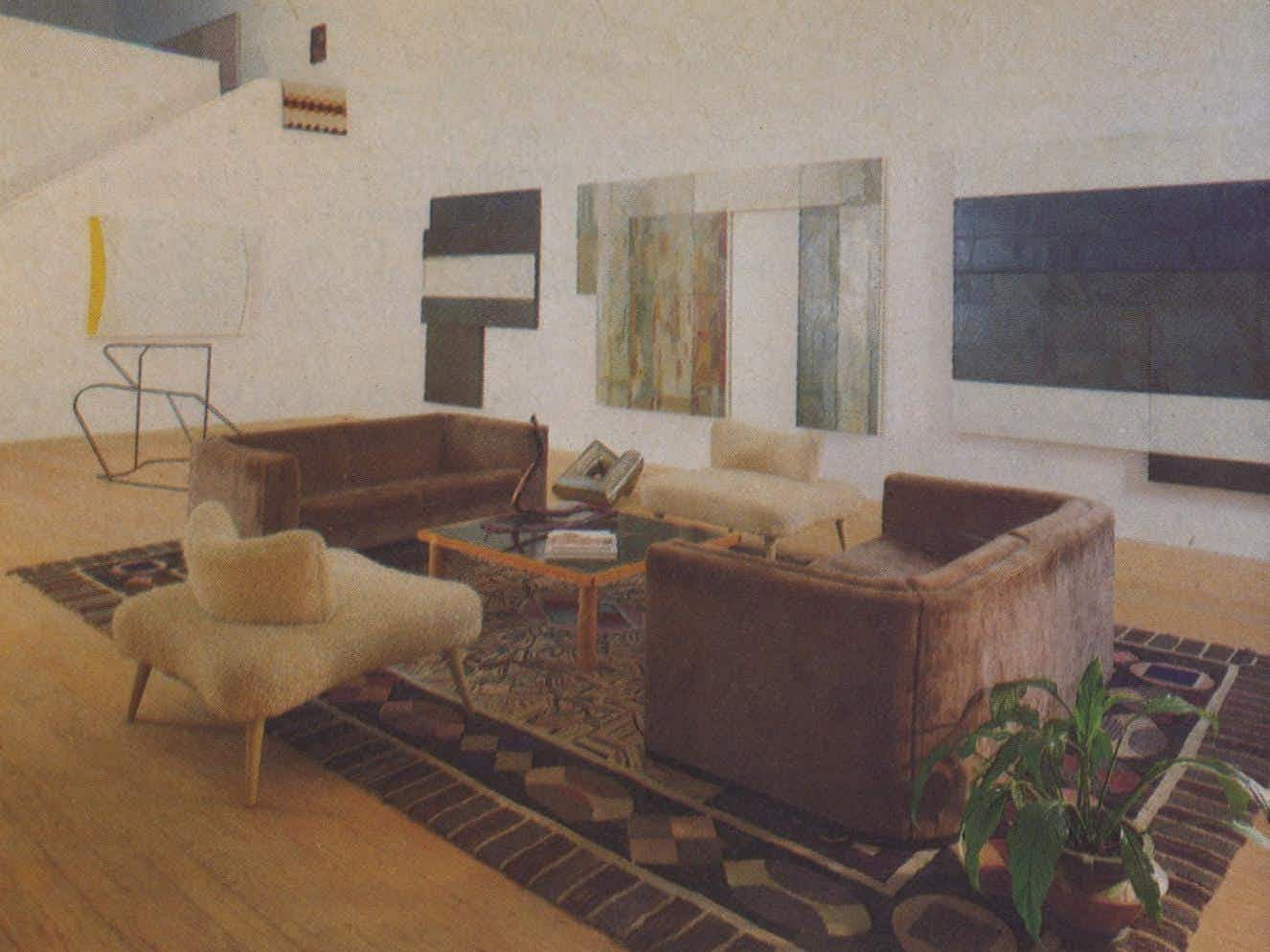 "The simple furnishings of the living room are set off by a large 19th-century French Canadian hooked rug. The new three-piece oil painting by David Novros has been hung to dry and is for sale. On the floor are metal sculptures by Clark Murray. A snakeroot sculpture sits on a ""tea table"" by Billy Al Bengston, and Jo Baer's ""M. Refractarius"" hangs on the stairwell wall."