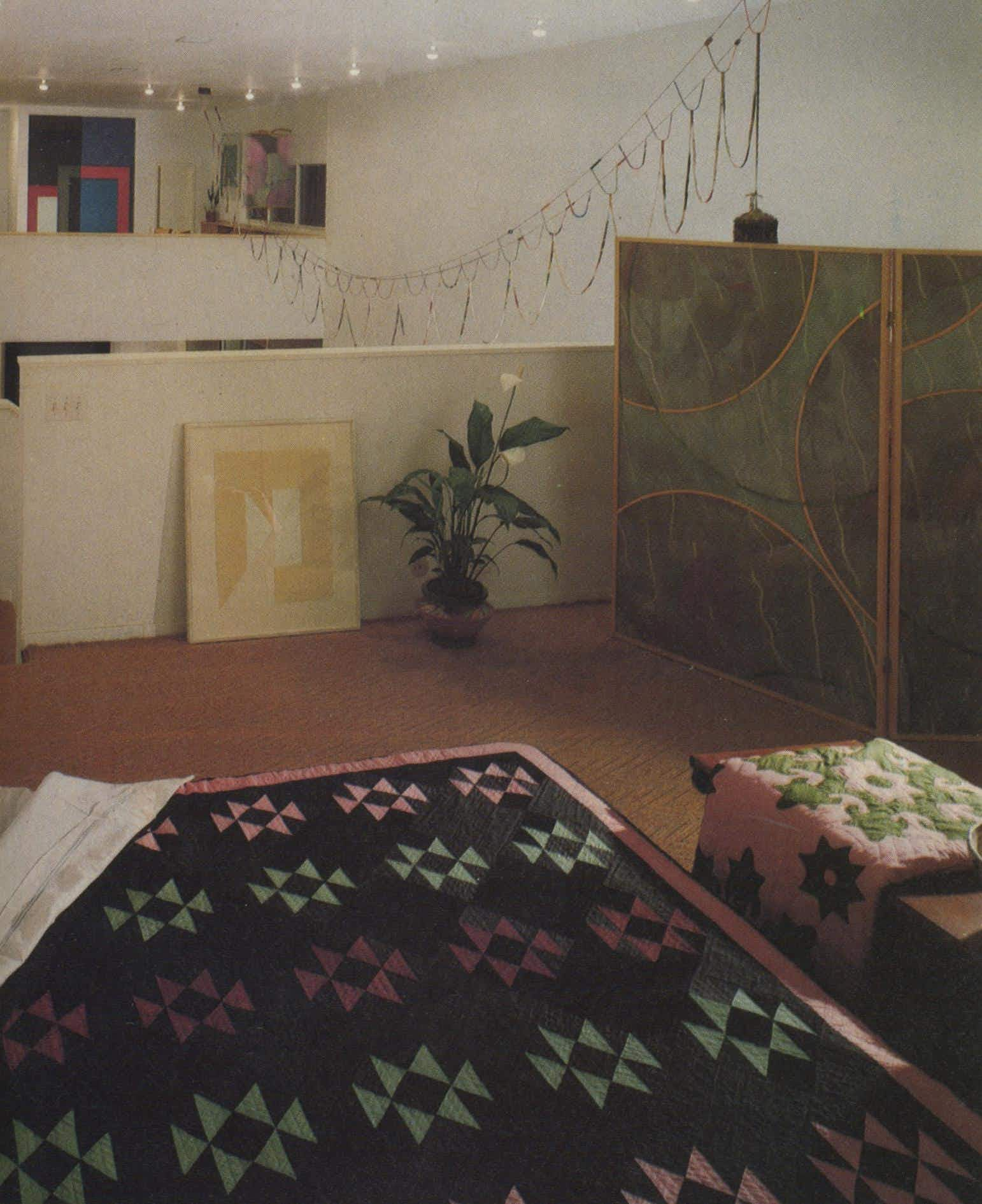 ": On the bed is a 19th-century Amish quilt from Ohio. The 1875 Terrace-style Navaho blanket on the stair rail is a collector's piece. The Billy Al Bengston screen (right) and Joe Goode oil (over the bed) pick up the colors of the quilt. Leaning against the wall is Gary Stephan's painting, ""Hours 3."""