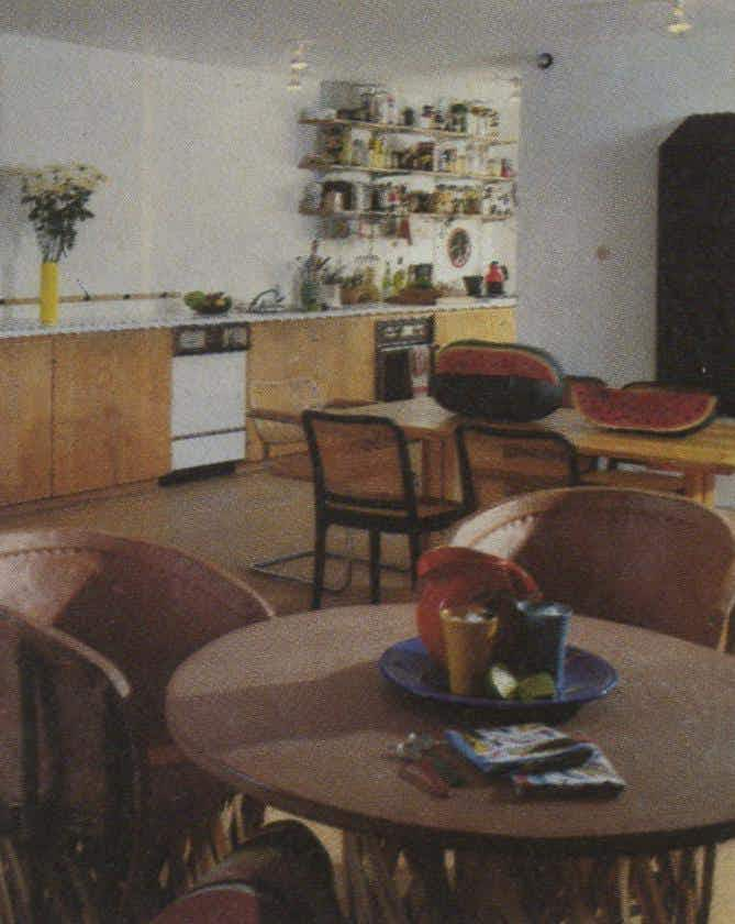 The open shelves over the kitchen counter hold an array of foods ranging from pasta to imported chutneys. In the foreground are a Mexican table and chairs of cowhide and split cedar.
