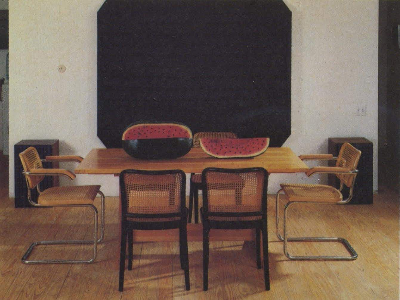 Ralph Humphrey's heavily textured black oil provides a dramatic background for the colorful watermelon centerpiece carved from cottonwood and painted by Felipe Archuleta. Around the table are original Cesca (light) and Thonet (black) chairs.