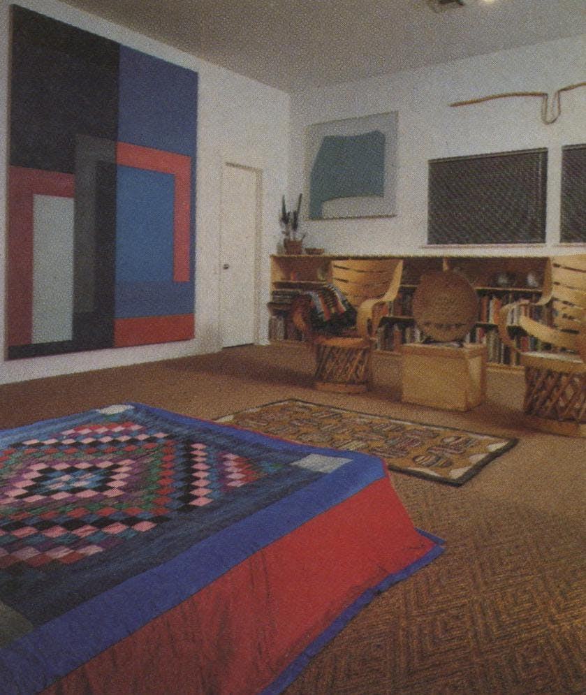 "David Novros' large canvas repeats the colors of the Amish quilt on the bed. The Mimbres and Sikyatki American Indian pottery on the first row of shelves date to 1300, but Peter Voulkos' 1973 plate is a perfect complement. Above the shelves is Gary Stephan's ""Garden Cycle 5."" The American hooked rug dates from the 19th century. Above the windows is a rope and twine creation by Chuck Arnoldi."