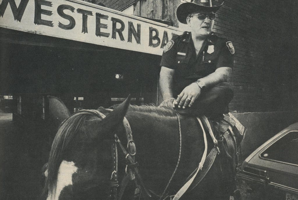 Some things never change. Justice in Cowtown is meted out by a lawman sitting tall in the saddle—J. D. Powers.