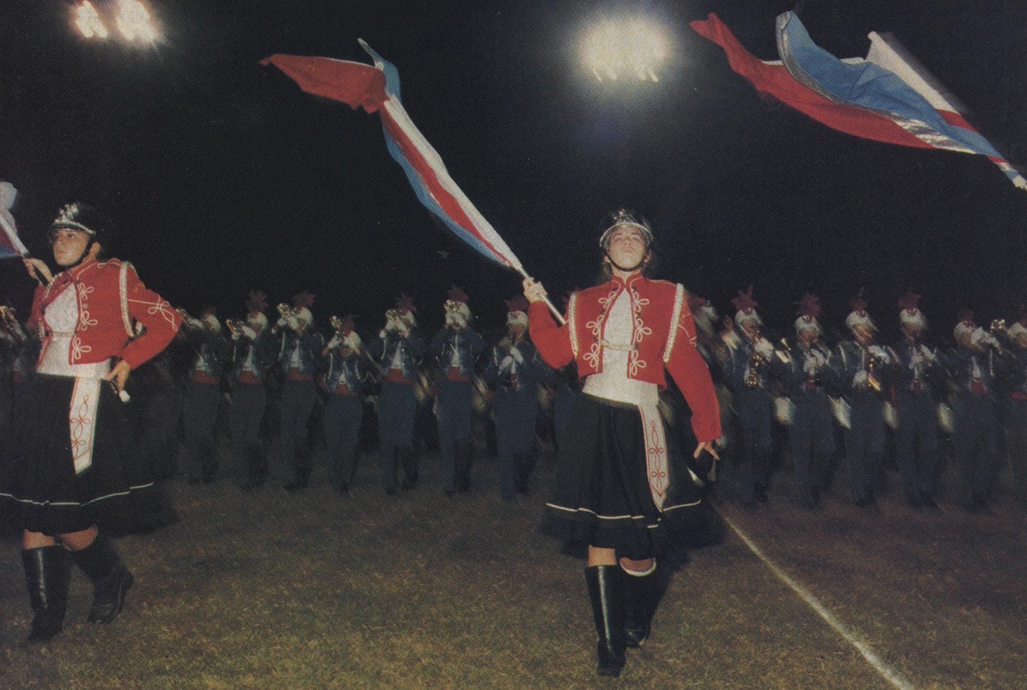 The flag bearers of neighboring Pearce High School strut arrogantly downfield. Note the asymmetry of their arms—bad form.