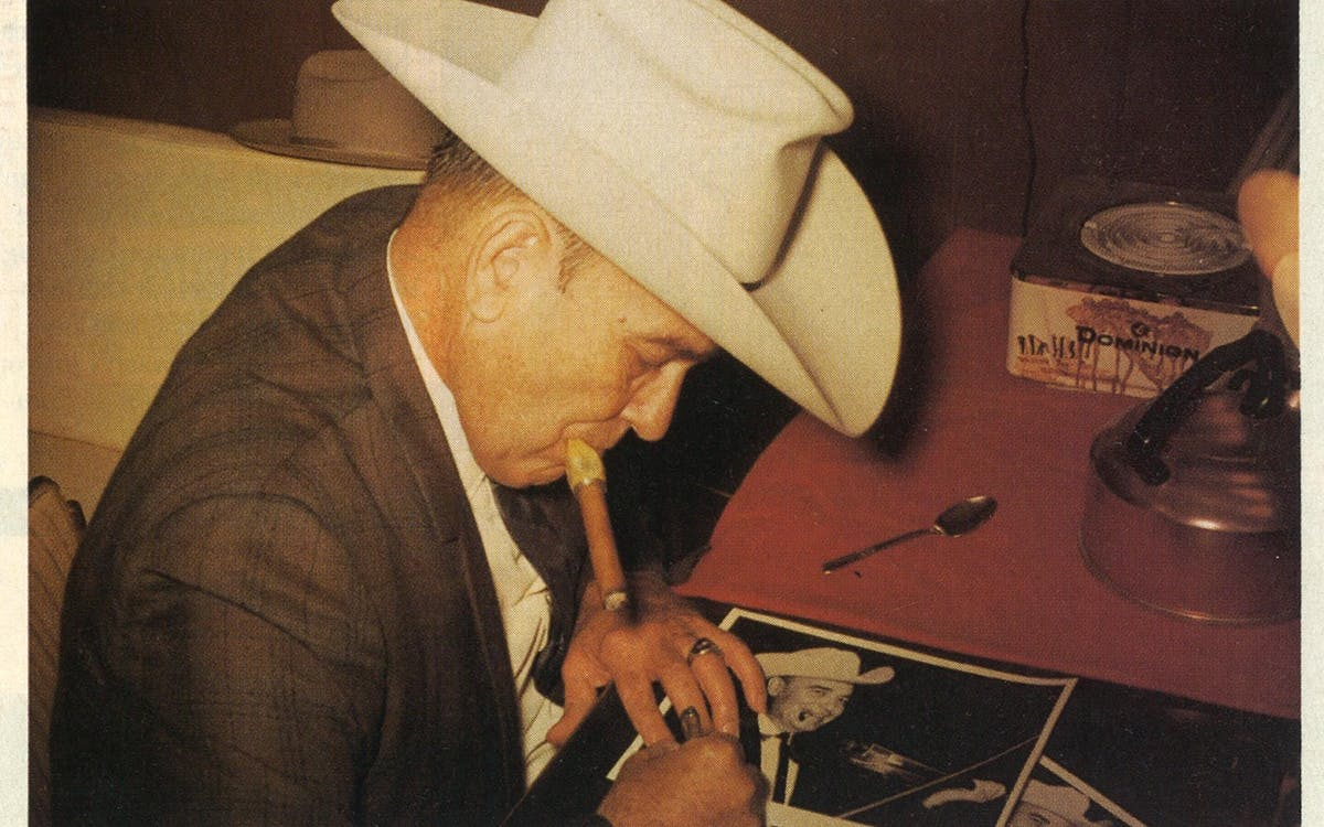 1966: Swing king Bob Wills takes a break from performing to smoke a cigar and sign some autographs at the New Cotton Club.
