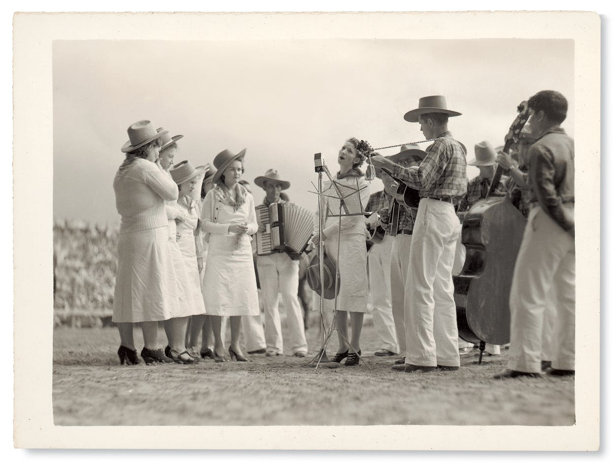 Accompanied by the Rhythmic Stringsters, yodeler Mozelle McDaniel leads the Goree Girls at the prison rodeo.