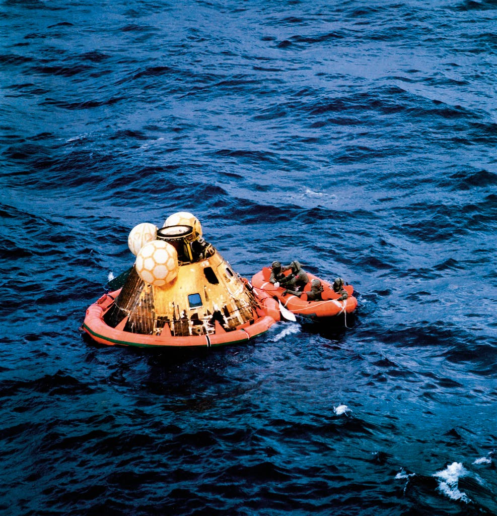 The astronauts prepare for a helicopter to pick them up shortly after splashdown in the Pacific Ocean southwest of Hawaii.