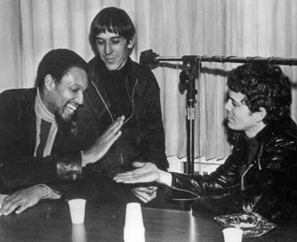 Wilson low-fives Lou Reed as Velvet Underground bandmate John Cale looks on during taping of MGM underground radio promotional disc The Factory, 1968.