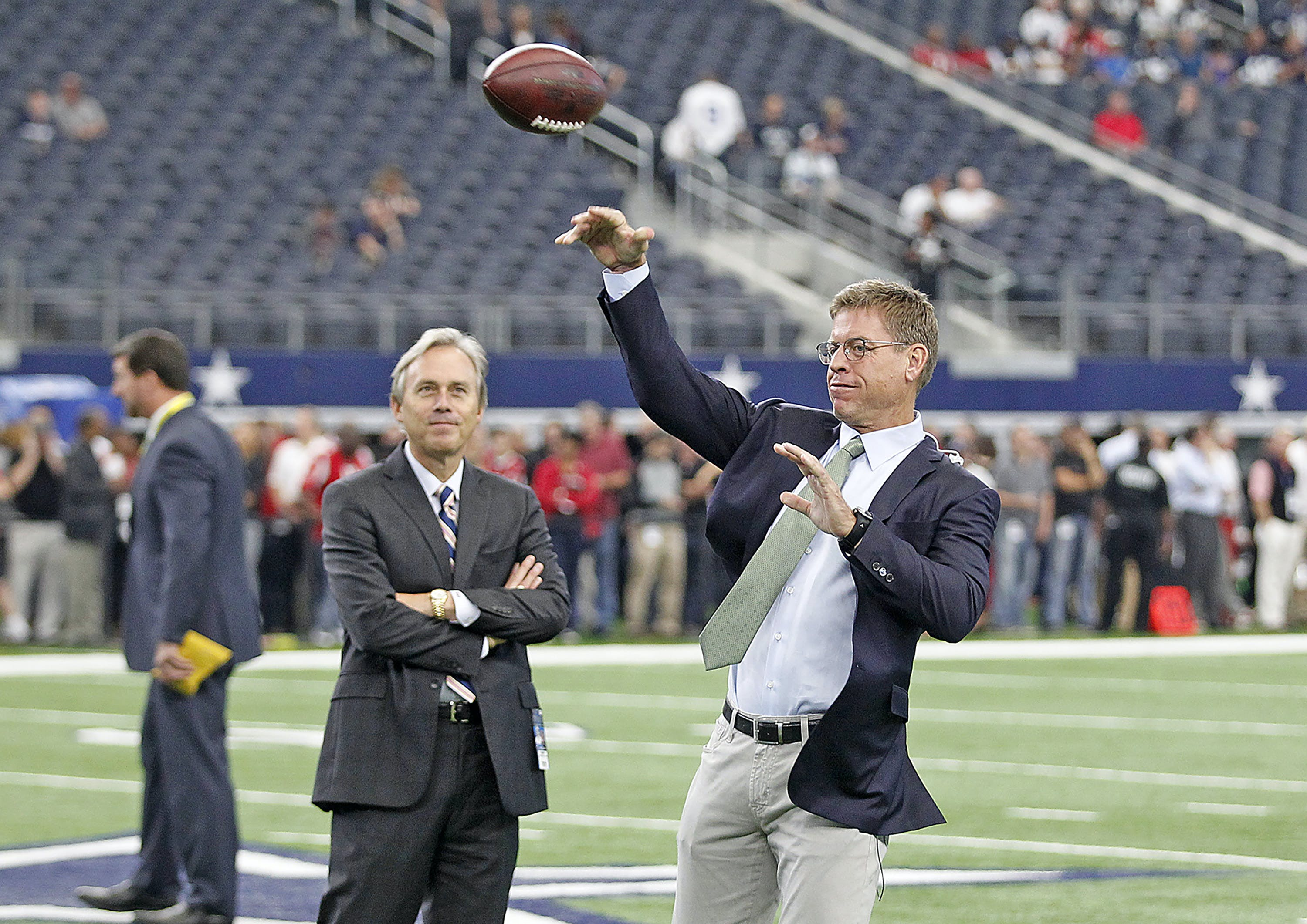 Fox Sports announcer Troy Aikman passes before an NFL game between the Dallas Cowboys against the Atlanta Falcons at AT&T Stadium in Arlington, Texas, Sunday, September 27, 2015.   The Falcons defeated the Cowboys, 39-28.  (James D. Smith via AP)