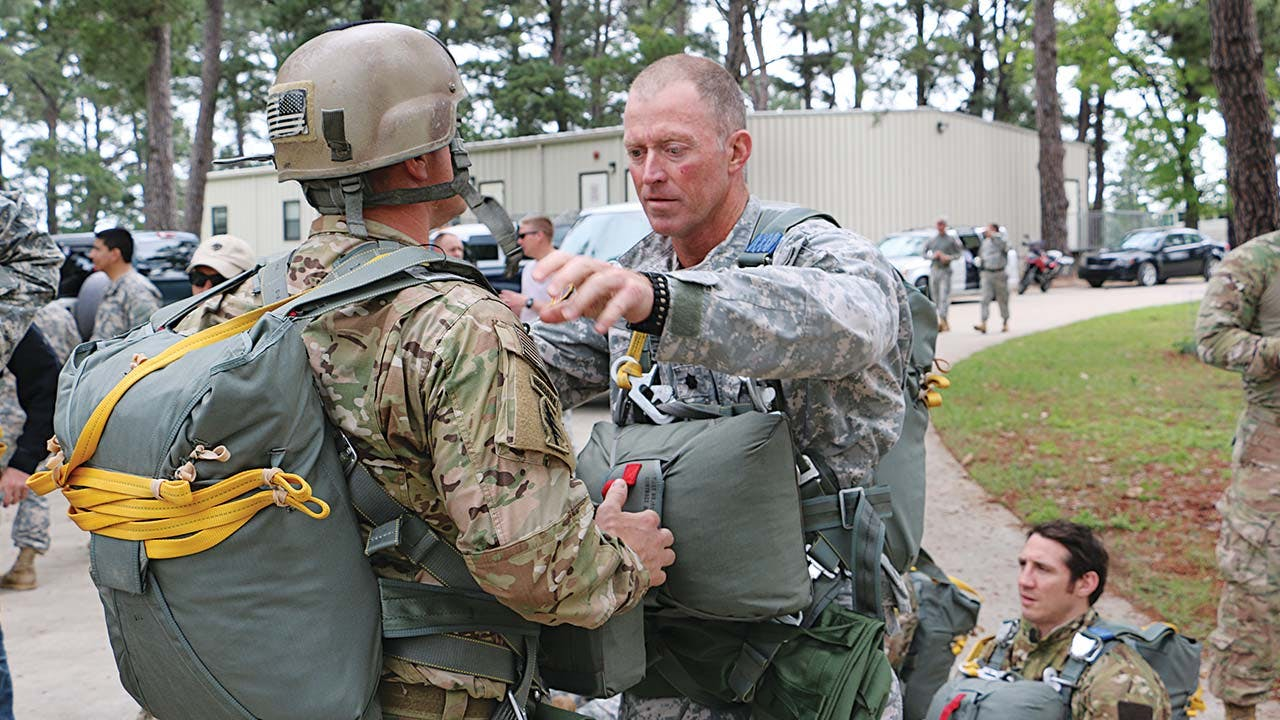 Tim Ochsner inspects one of his soldiers' parachute riggings.