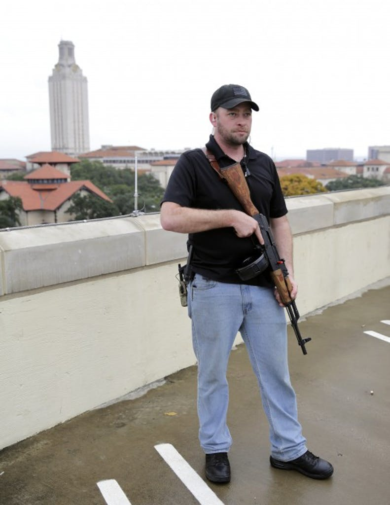 Gun rights activist Michael Short holds a gun as he prepares for a march near UT.