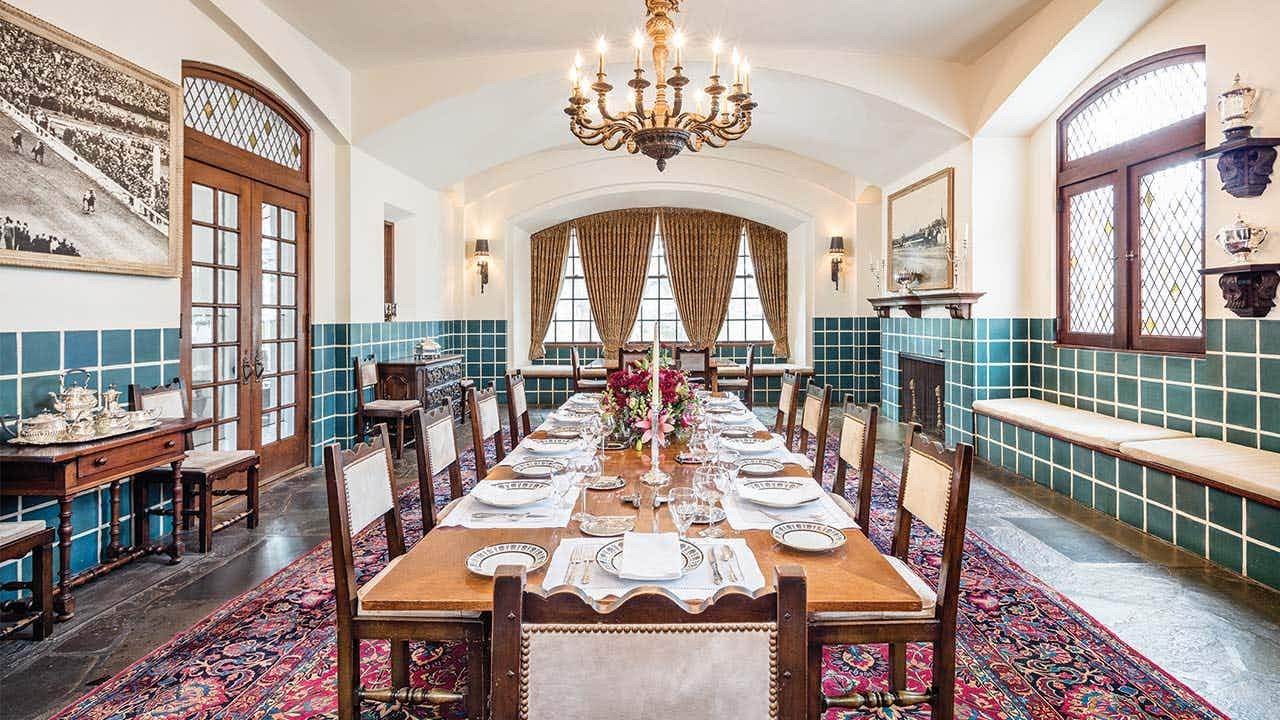 The formal dining room, with the table and chairs made by Tiffany, features blue-green tile wainscoting that was specially made at Henrietta's request. For grand occasions the table can seat fifty.