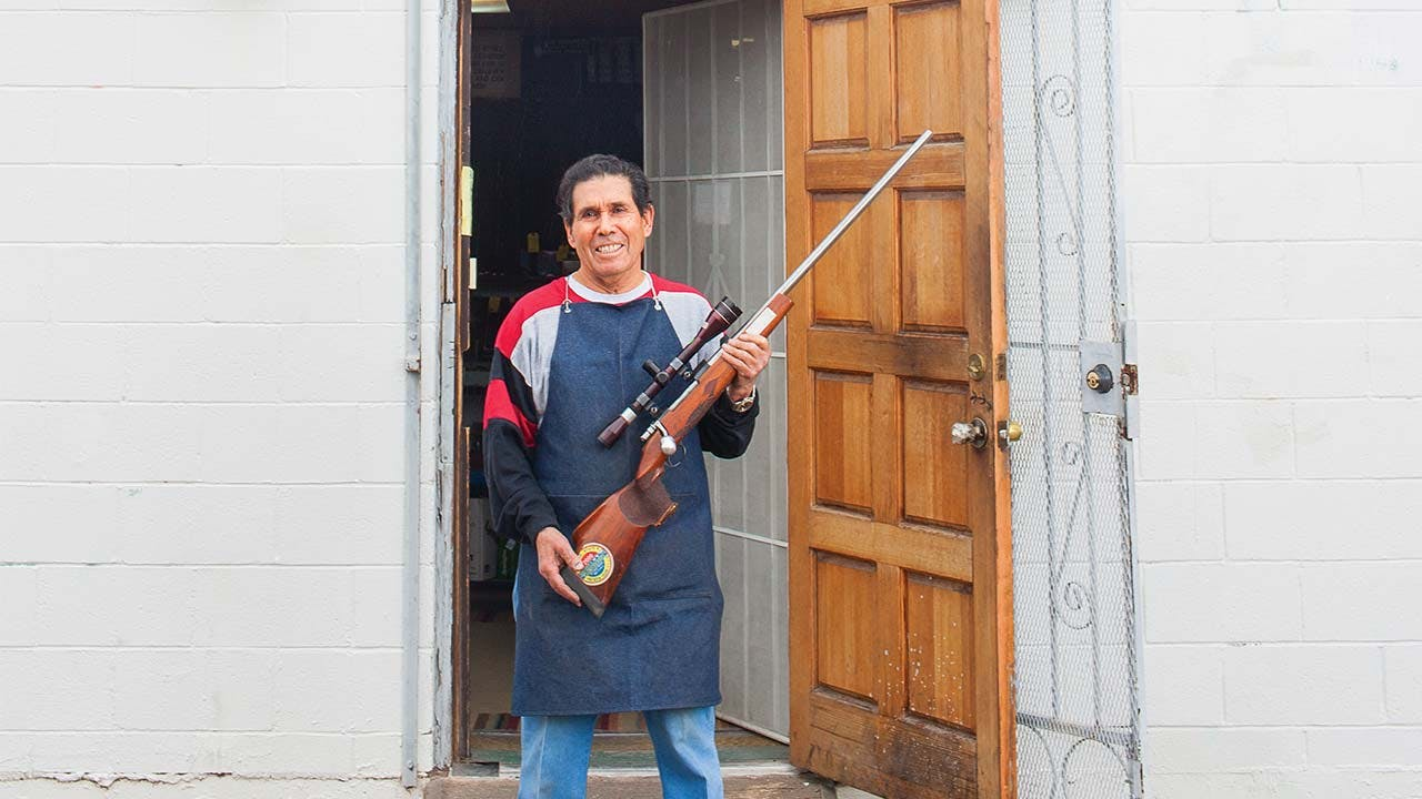 """Jesus """"Chuy"""" Aguirre outside his shop, in El Paso, on January 5, 2016, holding one of his own guns."""