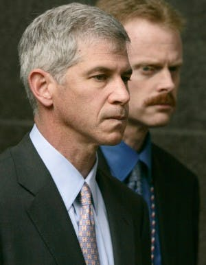 FILE - In this March 13, 2006 file photo, former Enron CFO Andrew Fastow, left, is escorted away from the federal courthouse by an officer in Houston at the end of his final day of testimony in the fraud and conspiracy trial of former Enron executives Kenneth Lay and Jeffrey Skilling. (AP Photo/Pat Sullivan, File)