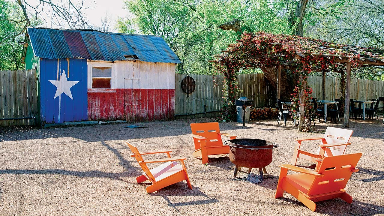 feature-WTSN-camp-comfort-exterior-fire-pit-chairs-texas-flag-building