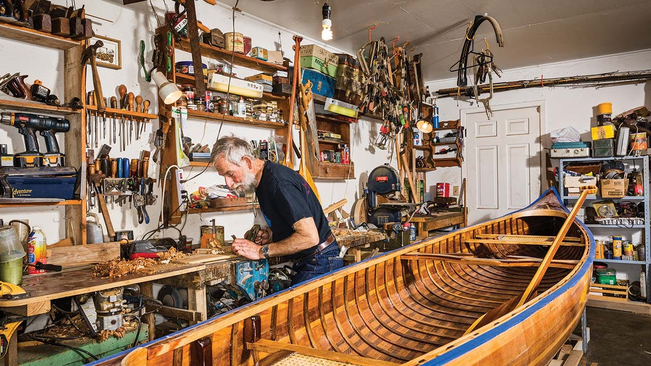 Bowen with a canoe awaiting its final sanding and varnish (boats start at $3,000).