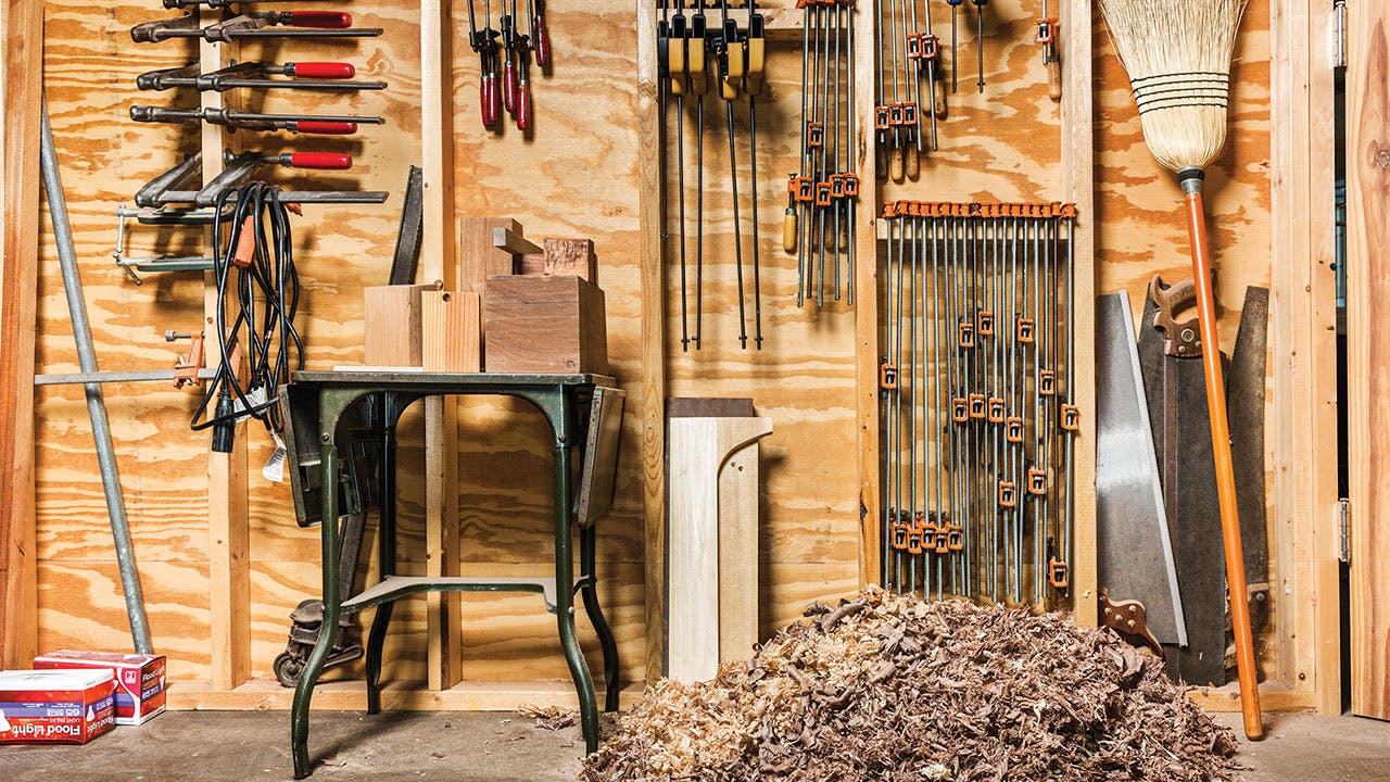 A heap of sawdust and wood shavings below a wall of clamps and saws.