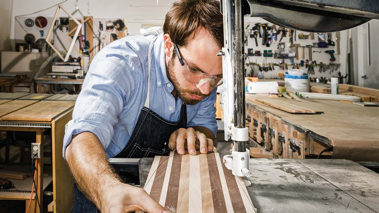 Eshelman using a band saw to cut a slab of reclaimed hardwoods into the shape of a board.
