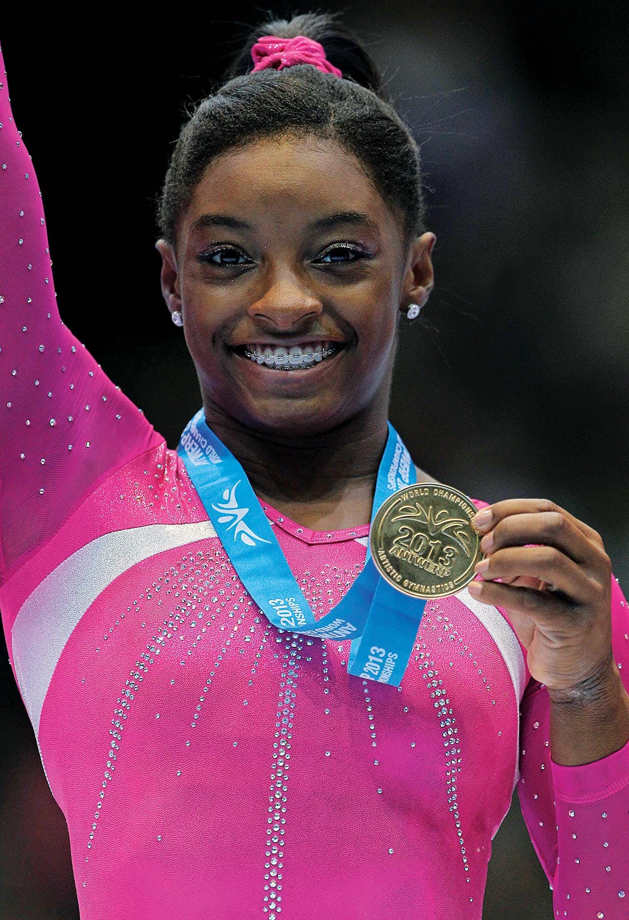 Biles shows her gold medal during the podium ceremony at the 2013 Worlds, in Antwerp.