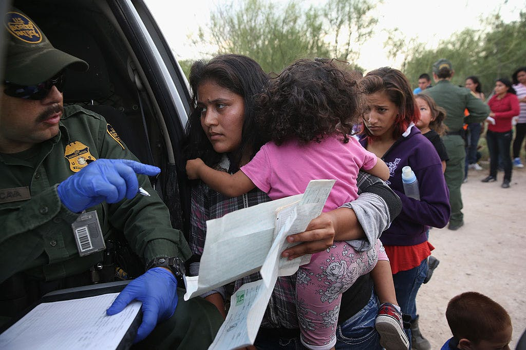 Immigrant Melida Patricio Castro from Honduras shows a birth certificate for her daughter Maria Celeste, 2, to a U.S. Border Patrol agent near the U.S.-Mexico border on July 24, 2014 near Mission, Texas.