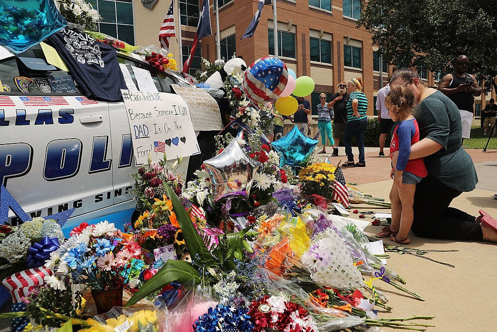 People visit a growing memorial at the Dallas police department's headquarters near the active crime scene in downtown Dallas following the deaths of five police officers on Thursday evening on July 9, 2016 in Dallas, Texas.