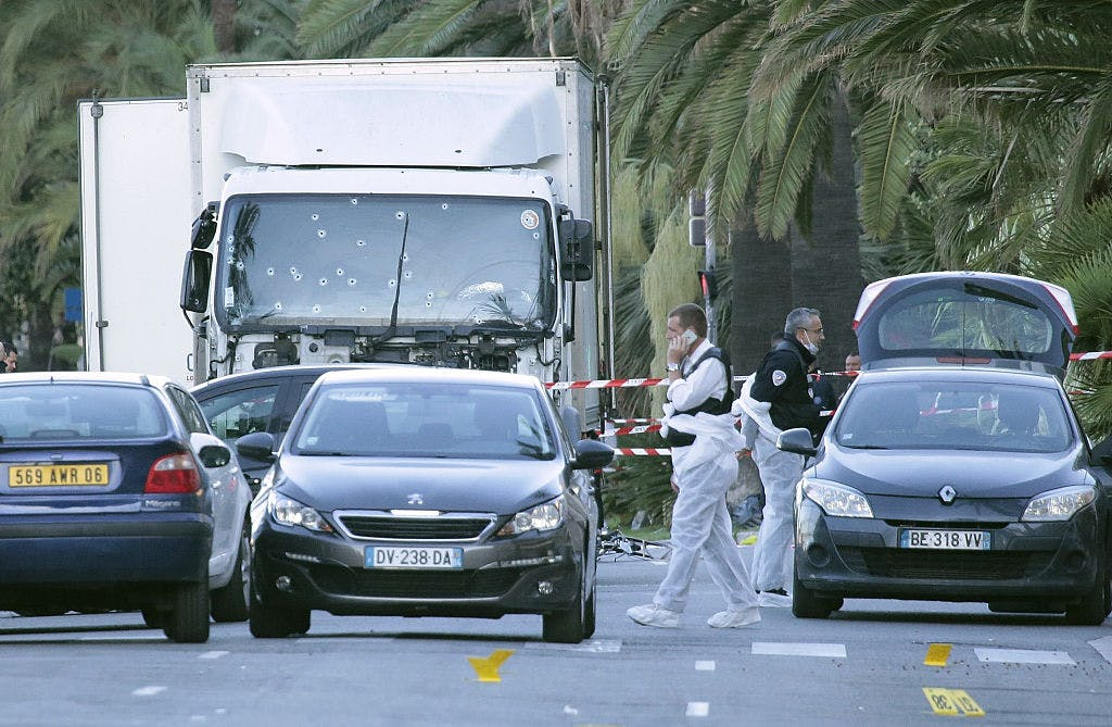 The police look for evidence near a truck on the Promenade des Anglais on July 15, 2016 in Nice, France. An attack in Nice where a man rammed a truck into a crowd of people left 84 dead.