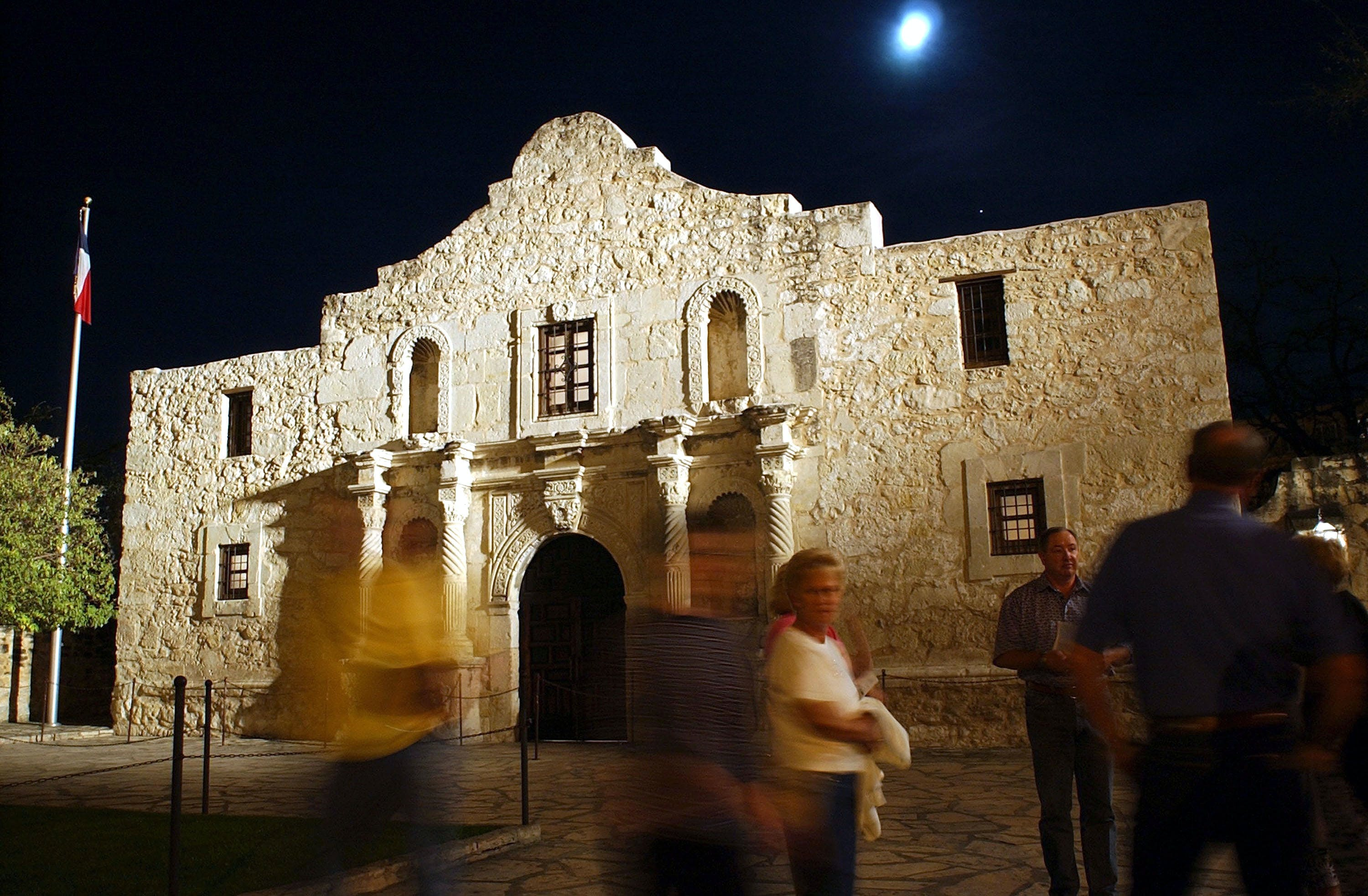Visitors walk around outside of the Alamo the night before the 168th Anniversary of the 1836 Fall of the Alamo March 5, 2004 in San Antonio, Texas.