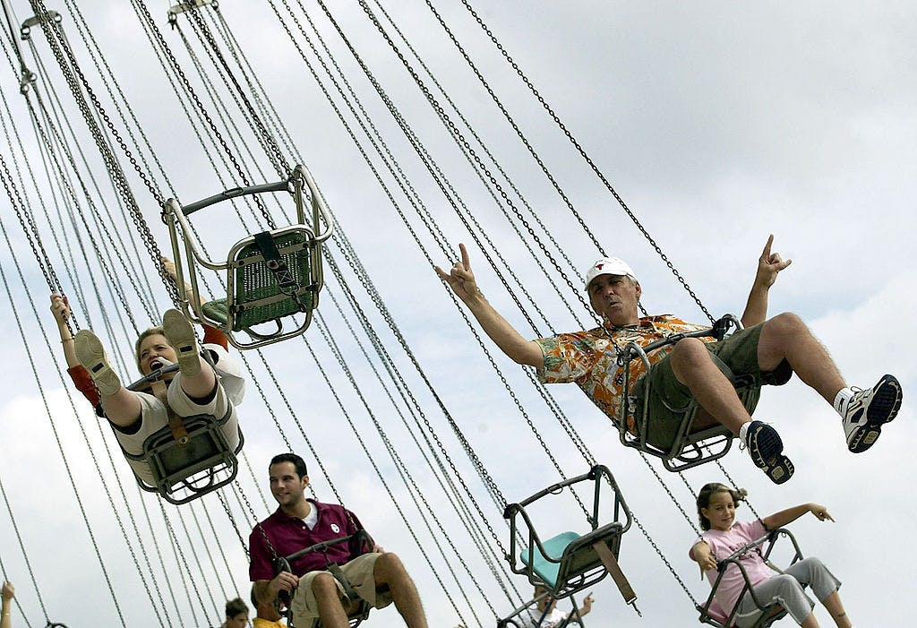 "University of Texas fan, Larry Parks, gives the ""hook em horns"" sign while riding the swings before the game against the Oklahoma Sooners and the Texas Longhorns during the State Fair of Texas on October 11, 2003 in Dallas, Texas."