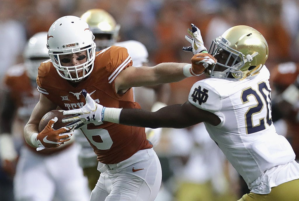 : Jake Oliver #6 of the Texas Longhorns stiff arms Shaun Crawford #20 of the Notre Dame Fighting Irish during the first half at Darrell K. Royal-Texas Memorial Stadium on September 4, 2016 in Austin, Texas.