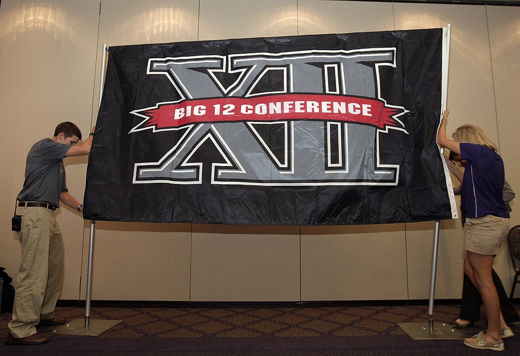 Texas Christian University sophomore Zach Boring (L), and freshman Laura Dunn raise a Big XII Conference banner before a press conference in which TCU accepted an invention to join the Big XII on October 10, 2011 in Fort Worth, Texas.