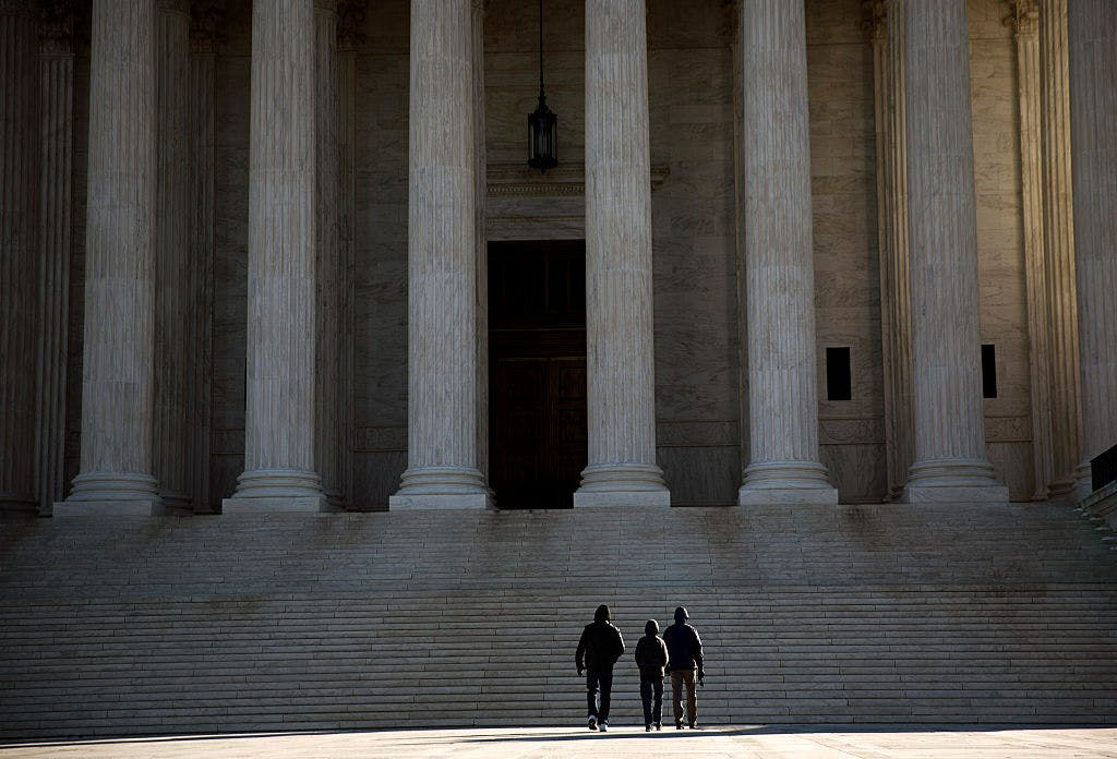 Visitors walk outside the U.S. Supreme Court on February 14, 2016 in Washington, DC.