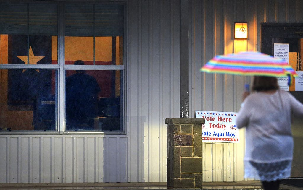 : A voter makes her way through morning rain to cast her ballot on November 8, 2016 in Annetta, Texas. After a contentious campaign season, Americans go to the polls today to choose the next president of the United States.