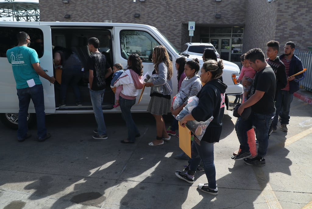"MCALLEN, TX - AUGUST 19: Immigrant families are transported to an ""Immigrant Respite Center"" after being released by the U.S. Border Patrol on August 19, 2016 in McAllen, Texas. After crossing the Rio Grande from Mexico into Texas, the families are taken into custody by the U.S. Border Patrol, given temporary legal documents and then sent by bus to their destination city in the United States, where they apply for political asylum. Many receive assistance from the Sacred Heart Catholic Church Immigrant Respite Center in McAllen before continuing their journey. (Photo by John Moore/Getty Images)"