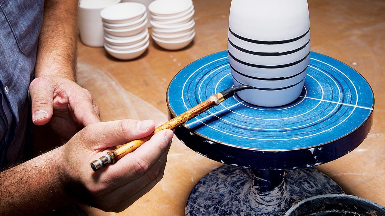 Kreeger hand-detailing a milk vase.