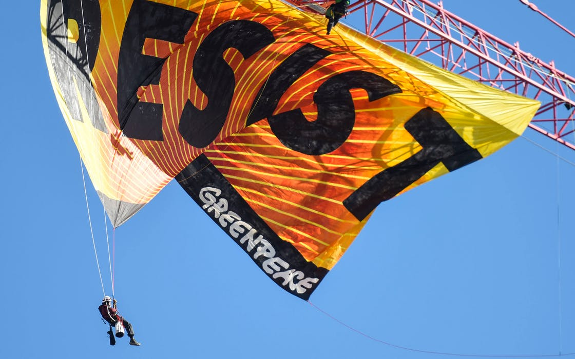Greenpeace activists hang from a construction crane with a banner that reads 'Resist', in Washington, DC on January 24, 2017.