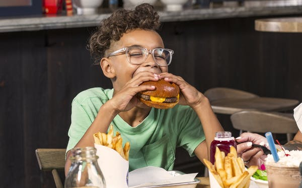 Kid eating a burger at Pearl's Bottling Department