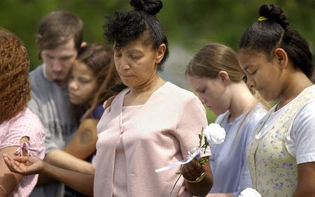 Sheila Martin, center, and her daughter Kimberly, far right, join in prayer at the grave site of some of the Branch Davidians, Saturday, April, 19, 2003 in Waco. The service was part of a 10-year-memorial service honoring the memory of those who died in the fire.