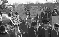 Anti-Vietnam War protesters, some carrying signs, rally on Texas Ranch Road 1, which leads to U.S. President Johnson's LBJ Ranch, in Stonewall, Texas, on Dec. 26, 1965.