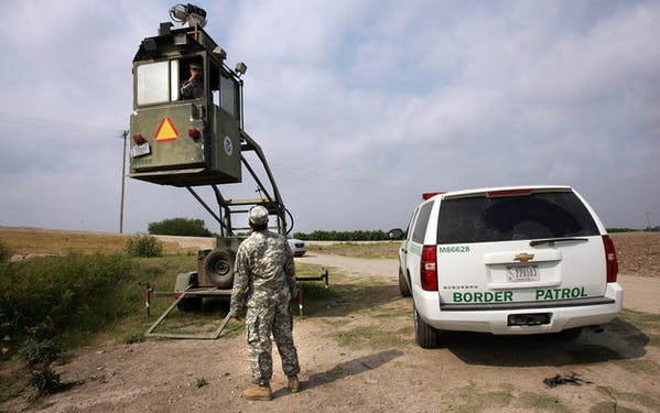 A member of the National Guard checks on his colleague inside a Border Patrol Skybox near the Hidalgo International Bridge in Hidalgo.