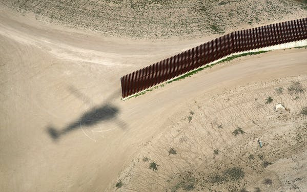A shadow from a U.S. Air and Marine Operations helicopter passes along the U.S.-Mexico border fence on February 21, 2018 in McAllen.