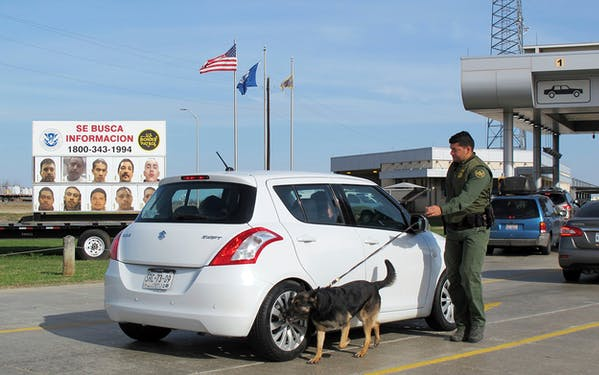 A Border Patrol agent uses a dog to inspect a car waiting to pass through the Laredo North vehicle checkpoint in Laredo on Friday, February 2, 2018.