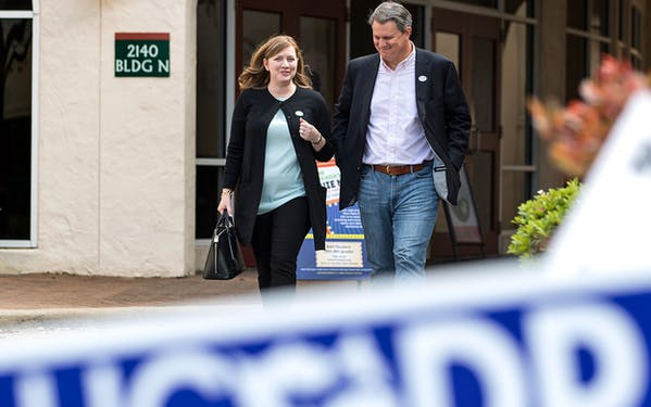 In this March 6, 2018, photo, Lizzie Pannill Fletcher and her husband, Scott Fletcher, walk out of the polling place at St. Anne's Catholic Church after voting in the primary election in Houston. Fletcher is up against Laura Moser in the Texas 7th Congressional District democratic primary runoff Tuesday, May 22, 2018.