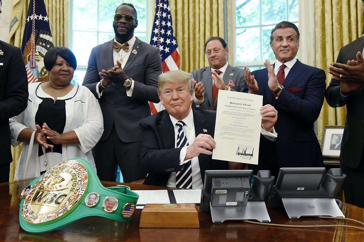US President Donald Trump holds a signed Executive Grant of Clemency for boxer 'Jack Johnson ' in the Oval Office of the White House on May 24, 2018 in Washington, DC. Attending the event from L to R Linda Haywood, Great great niece of Jack Johnson, Deontay Wilder, Keith Frankel, Sylvester Stallone, and Lennox Lewis.