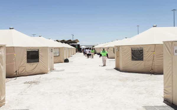 Detainees walk in a line at the HHS' unaccompanied alien children program facility at Tornillo, Texas.