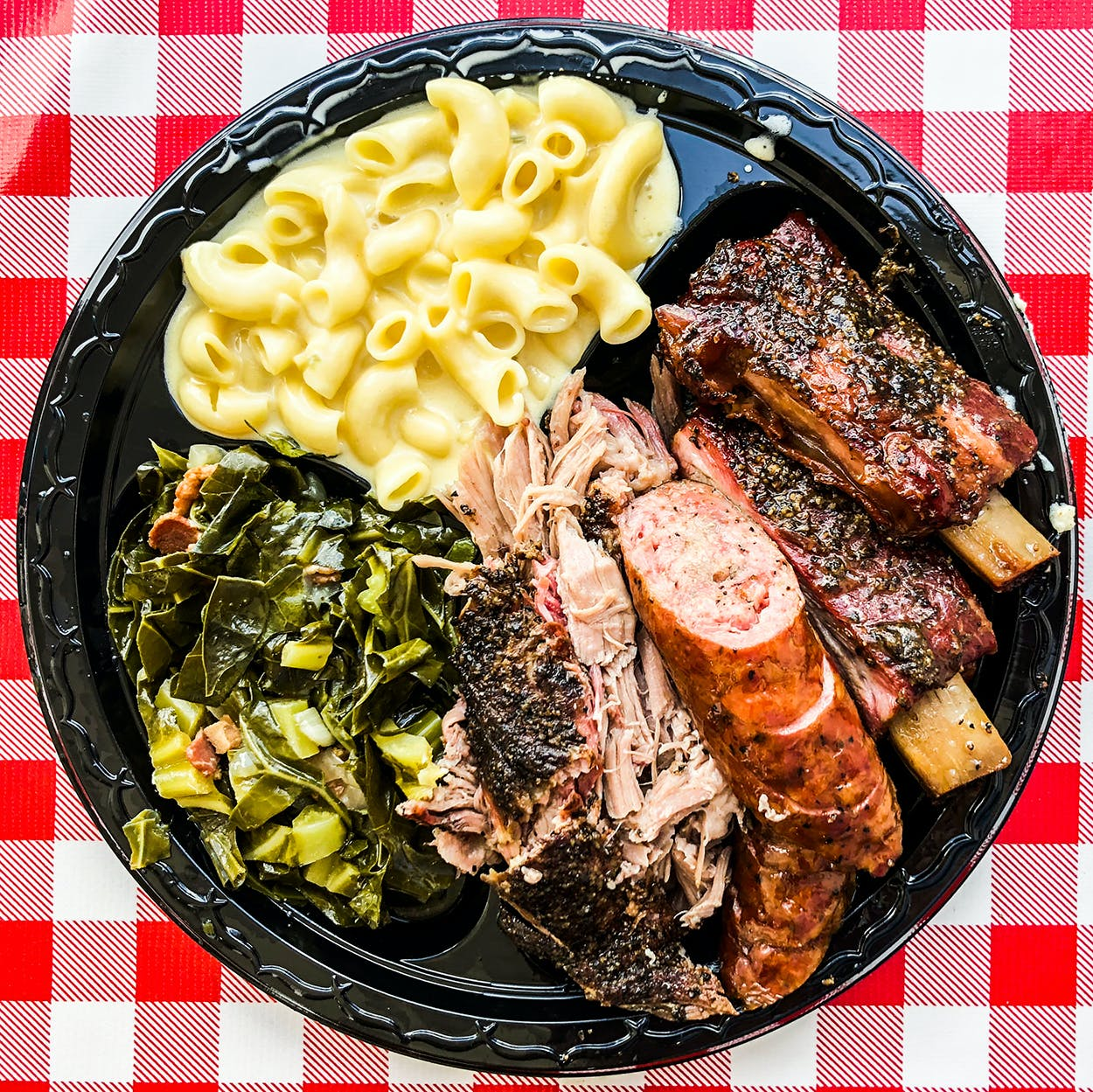 Collard greens with bacon and creamy mac and cheese served alongside pork shoulder, sausage and pork ribs from LJ's BBQ in Brenham.