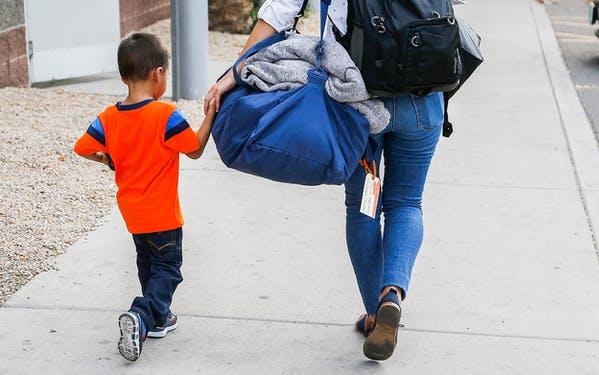 Three-year-old Jose Jr., from Honduras, is helped by a representative of the Southern Poverty Law Center as he is reunited with his father Tuesday, July 10, 2018, in Phoenix.