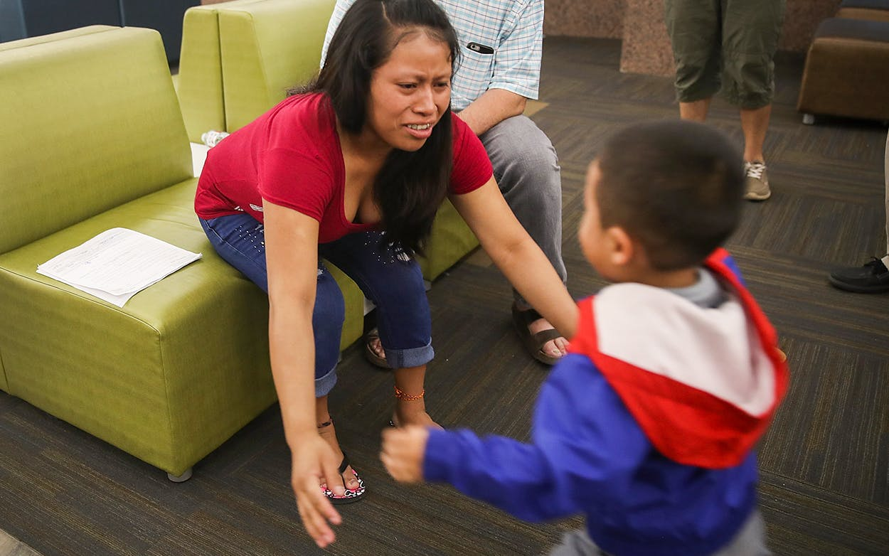 A woman, identified only as Maria, reaches for her son Franco, 4, as they are reunited at the El Paso International Airport on July 26, 2018 in El Paso.