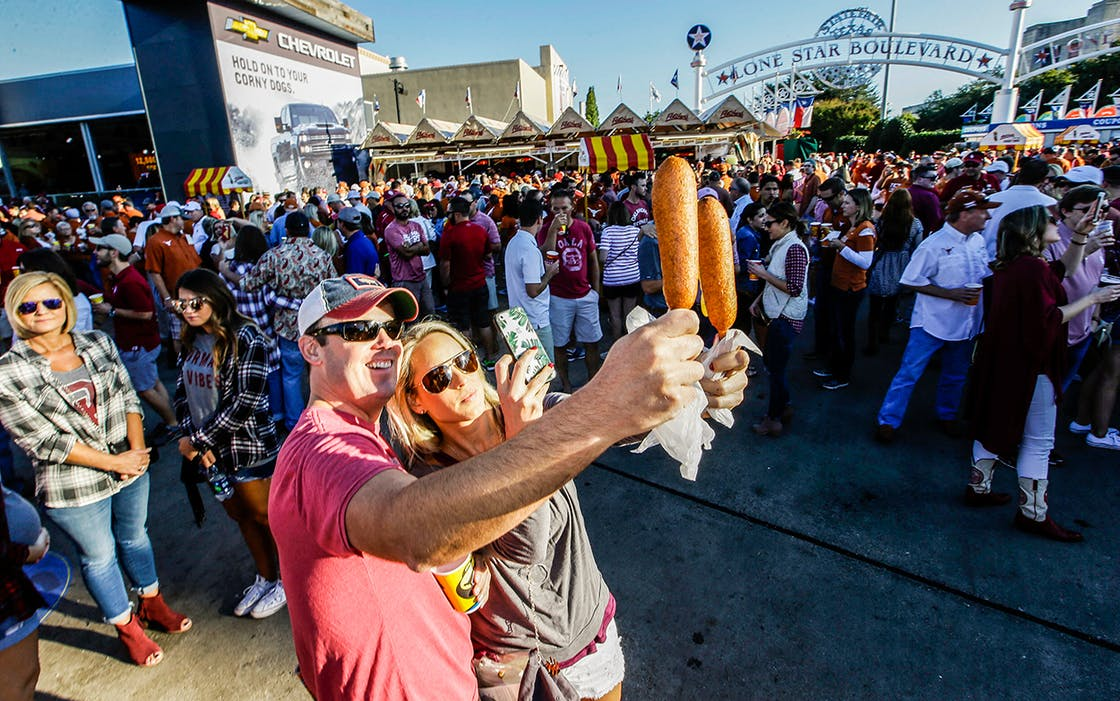 Gwin Huey, right, and her husband Ryan Huey make a photo of their corn dogs at the state fair before an NCAA college football game Saturday, Oct. 8, 2016.