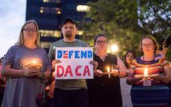 Martha Waggonner, Walker Waggonner, Katie Powell and Gail McGlothin stand in silence holding candles and signs during a silent vigil in honor of Deferred Action for Childhood Arrivals (DACA) at T.B. Butler Fountain Plaza in Tyler, Texas, on Tuesday, Sept. 5, 2017.