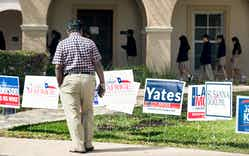 A voter stops to look at primary election signs outside the polling place at St. Anne's Catholic Church on Tuesday, March 6, 2018, in Houston.